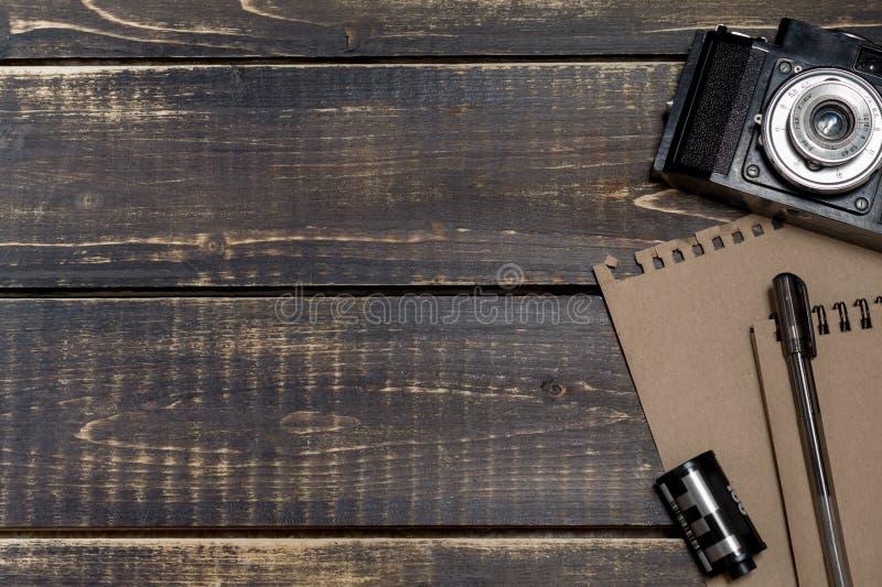 Gammal kamera, en notepad för anmärkningar och en film på en mörk träbaksida royaltyfri fotografi