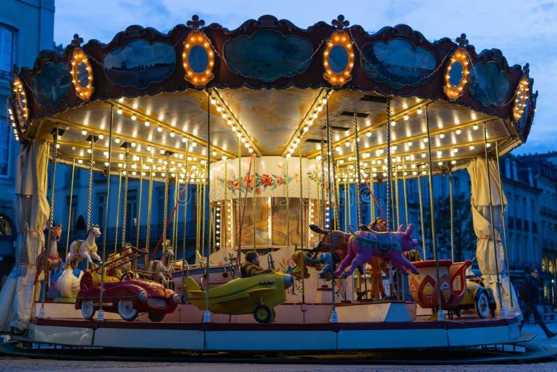 Gammal karusell för ung pojkeridning på natten med ljusa ljus arkivbilder