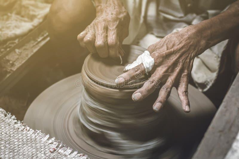 Gammal keramiker som gör bunken i krukmakeriarbetsbakgrund Gamal man som gjuter lera med hemslöjd royaltyfri fotografi
