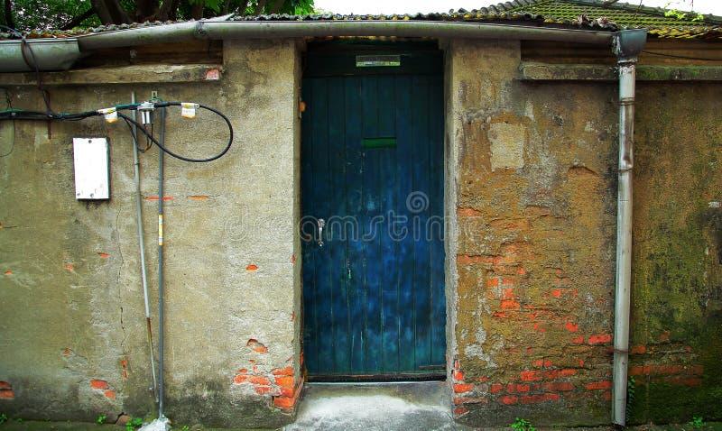 Gammal kinesisk husvägg med den blåa dörren arkivfoton