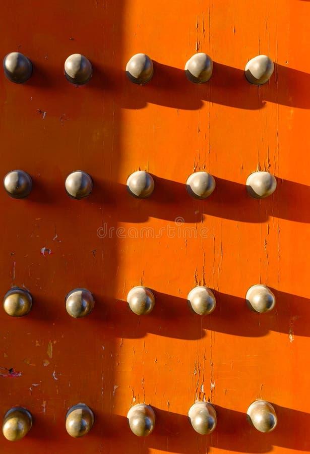 Gammal kinesisk trädörr för röd färg med metallknoppbakgrund arkivfoto