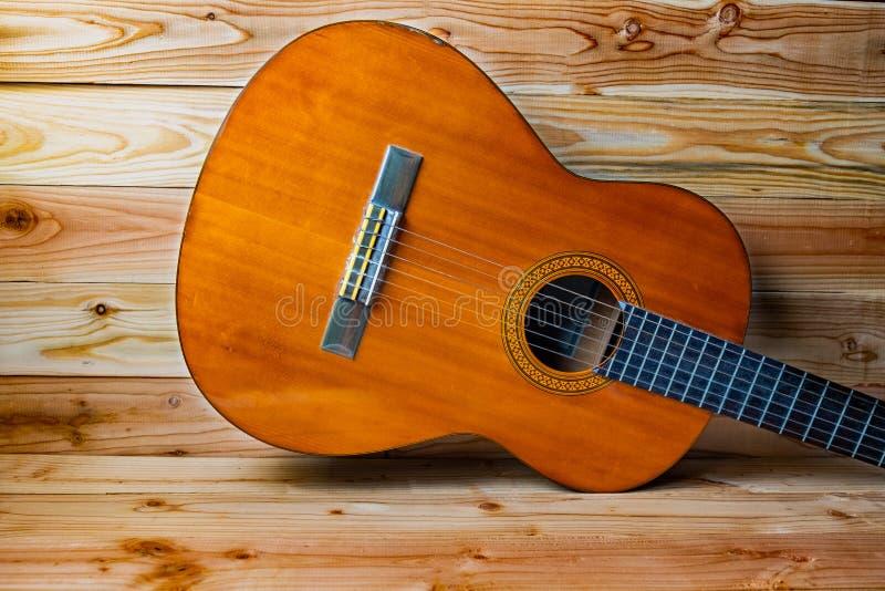 Gammal klassisk gitarr på träbakgrund arkivfoton