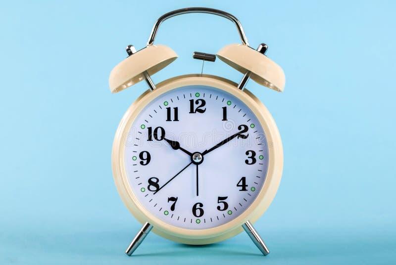 Gammal klocka med klockor som isoleras på blå bakgrund royaltyfri bild