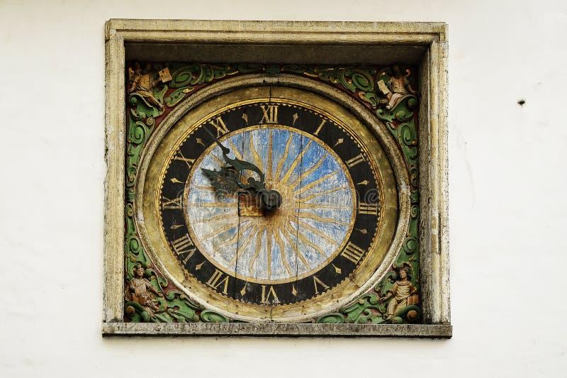 Gammal klocka på väggen av kyrkan i den gamla staden royaltyfri bild