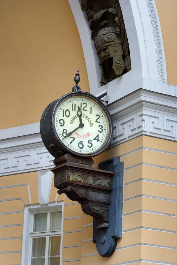 Gammal klocka under båge av byggnaden för allmän personal i St Petersburg Ryssland royaltyfri fotografi