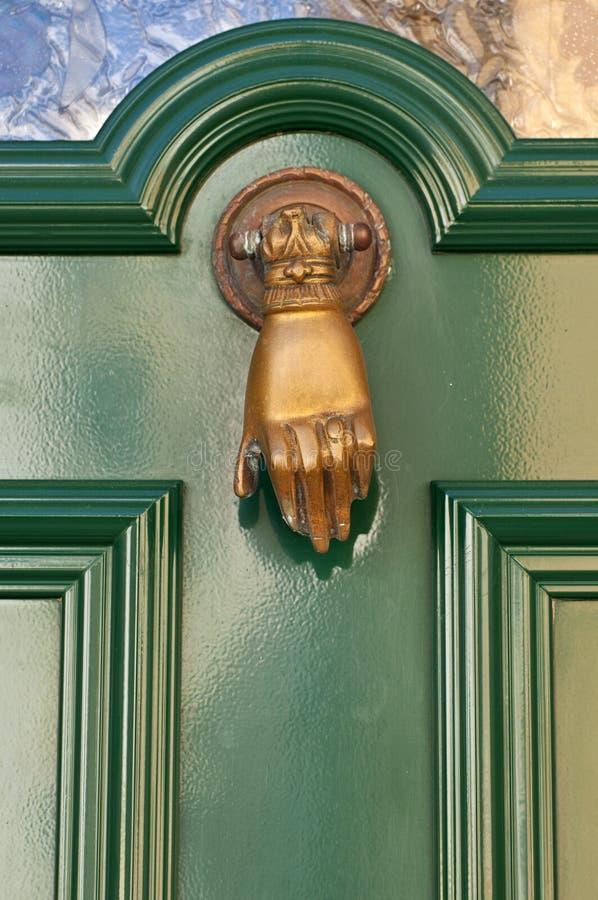 Gammal knackare i formen av en hand på en dörr arkivfoton