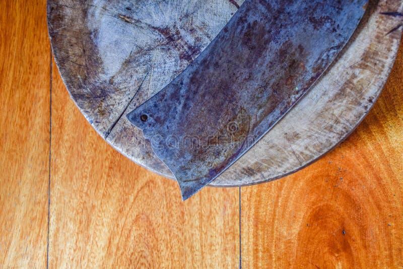 Gammal kniv som förläggas på den gamla skärbrädan för att skiva kött eller grönsaker på brunt trä royaltyfri bild
