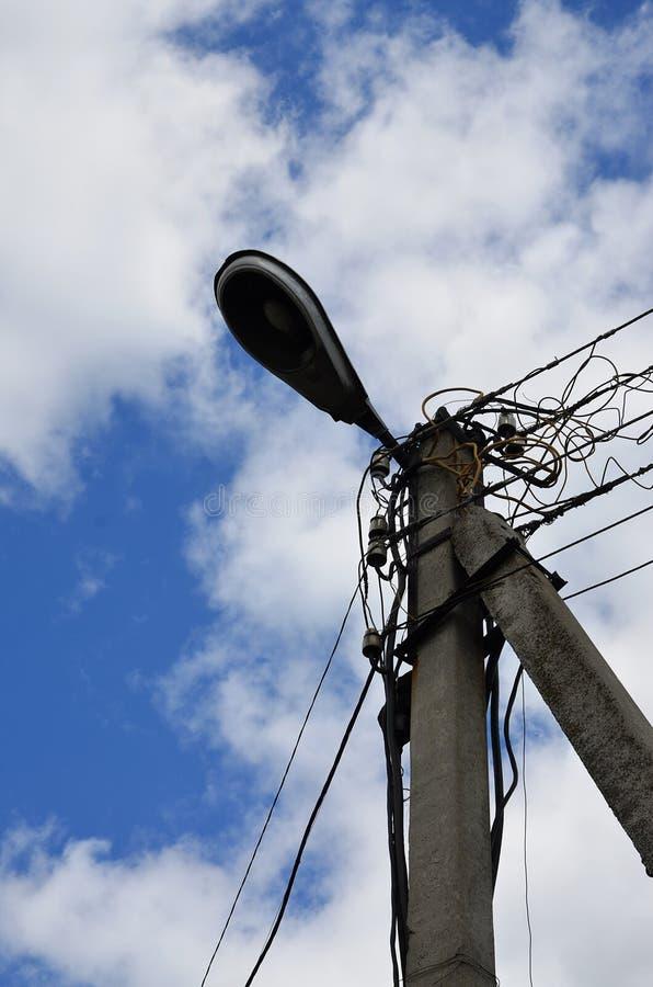 Gammal konkret elektrisk pol för överföring av bunden elektricitet med lampstolpen på en bakgrund av en molnig blå himmel Föråldr fotografering för bildbyråer