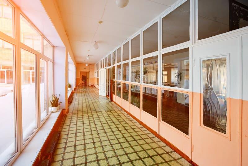 Gammal korridor inom skolabyggnaden Med järnbatterier och träfönsterramar arkivbilder