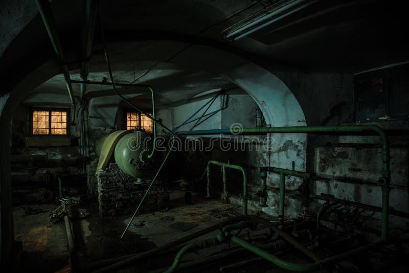 Gammal kuslig källare av den övergav asylen Gammal rutten kokkärl som värmer rör royaltyfri foto