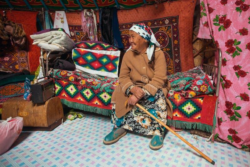 Gammal kvinna från Kazakhfamiljen av jägare med att jaga den deras insidan för guld- örnar mongolianen Yurts arkivfoto