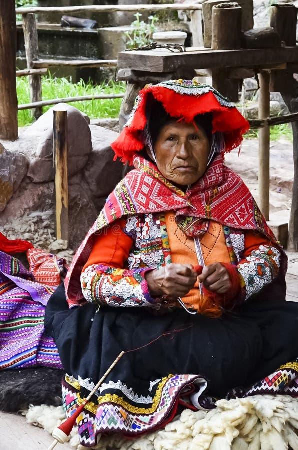 Gammal kvinna i den peruanska dräkten som väver alpacatröjan royaltyfri foto