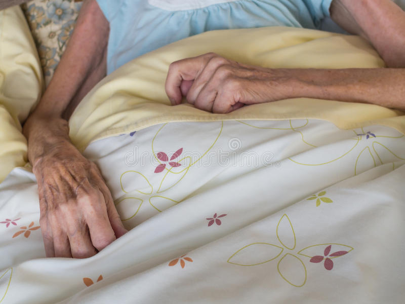 Gammal kvinna i en säng royaltyfri bild