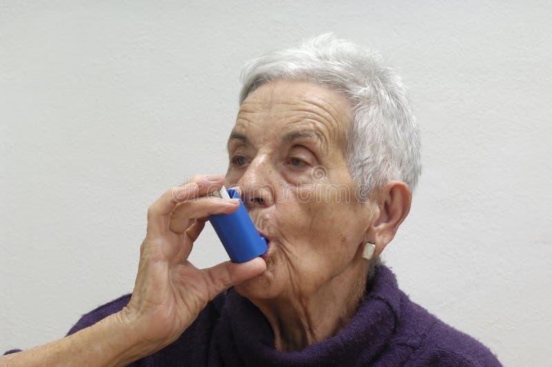 Gammal kvinna med en inhalator royaltyfri foto
