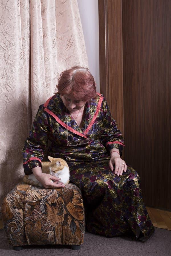 Gammal kvinna med en katt i henne hem arkivfoto