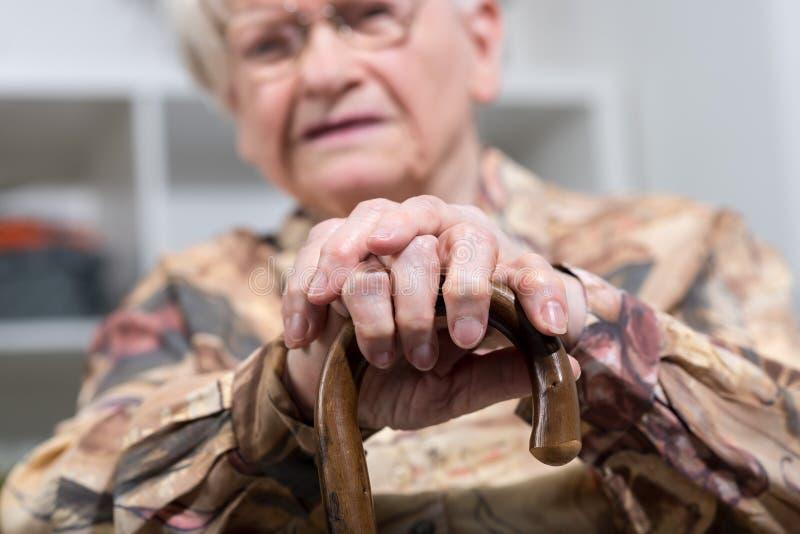 Gammal kvinna med hennes händer på en rotting royaltyfri bild