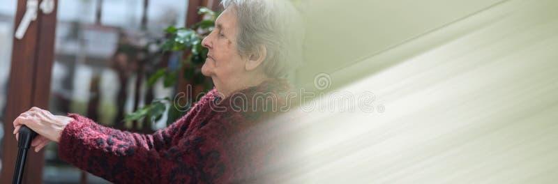 Gammal kvinna med hennes h?nder p? en rotting; panorama- baner royaltyfri fotografi