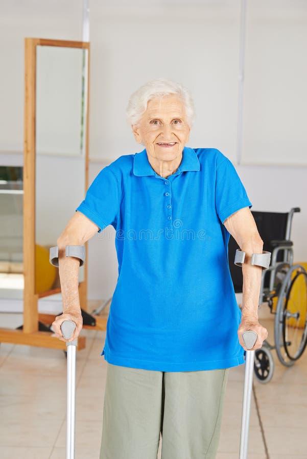 Gammal kvinna med kryckor i sjukgymnastik arkivfoto