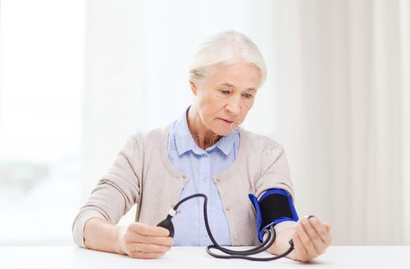 Gammal kvinna med tonometer som kontrollerar blodtryck royaltyfria bilder