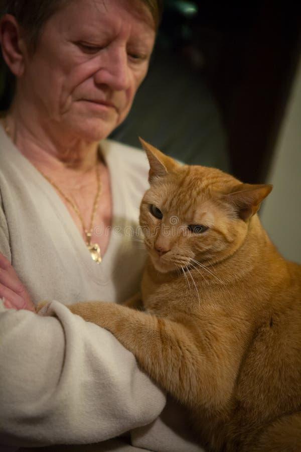 Gammal kvinna och hennes katt arkivfoto