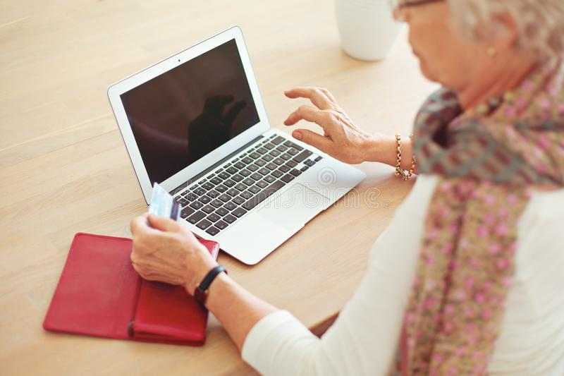 Gammal kvinna som använder bärbara datorn med den tomma skärmen arkivfoton