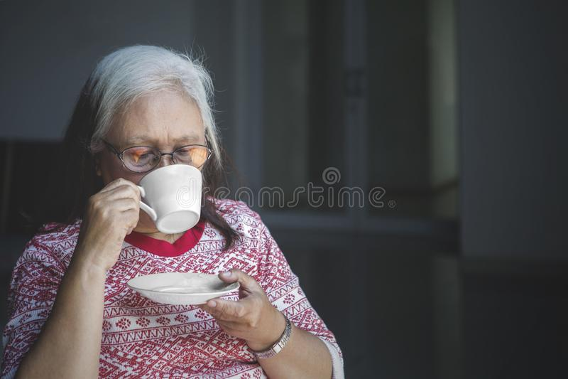 Gammal kvinna som dricker en kopp av varmt te royaltyfria foton