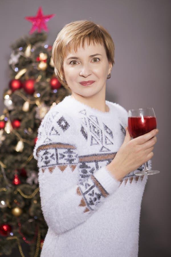 Gammal kvinna som firar det nya året som står nära julträd på fotografering för bildbyråer