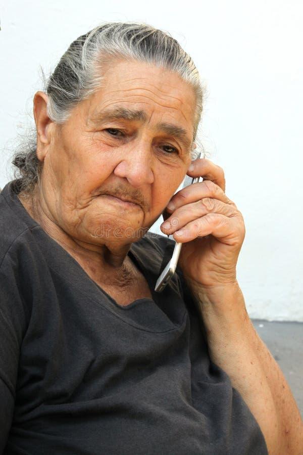 Gammal kvinna som gör en appell med en smartphone royaltyfri bild