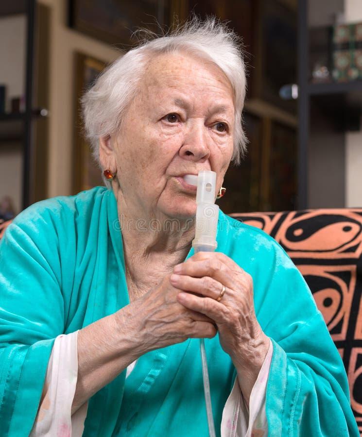 Gammal kvinna som gör en inandning arkivbild