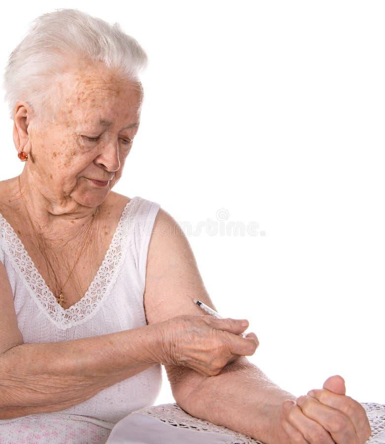 Gammal kvinna som ger sig en injektion av insulin royaltyfri foto