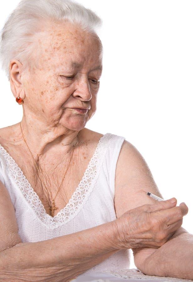 Gammal kvinna som ger sig en injektion av insulin royaltyfri fotografi