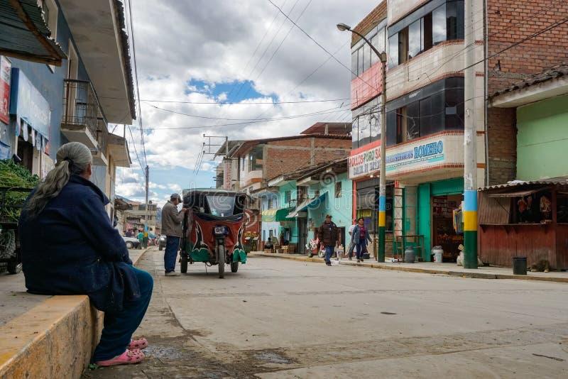 Gammal kvinna som håller ögonen på ongoingsna på den huvudsakliga gatan av Chavin de Huantar på en typisk upptagen vardag arkivbild