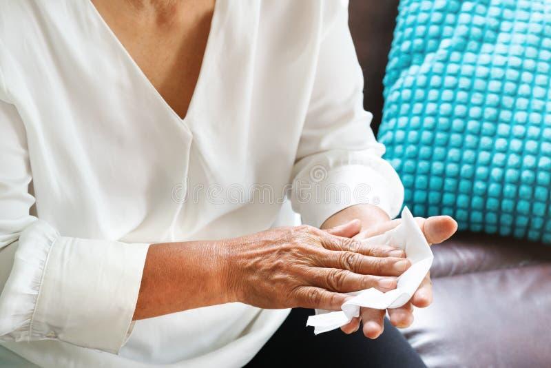 Gammal kvinna som hemma gör ren hennes händer med vitt mjukt silkespapperpapper royaltyfri fotografi