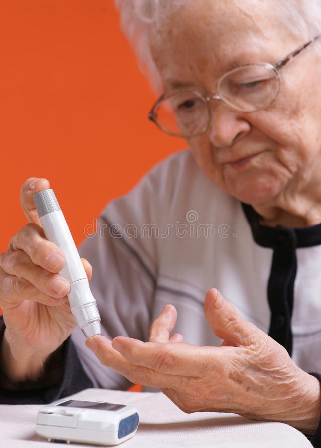 Gammal kvinna som kontrollerar jämnt socker arkivfoton