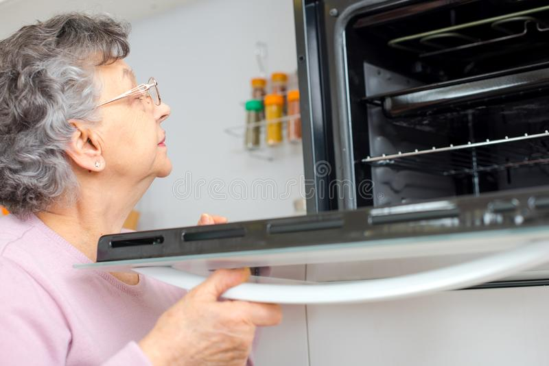 Gammal kvinna som kontrollerar ugnen royaltyfri foto