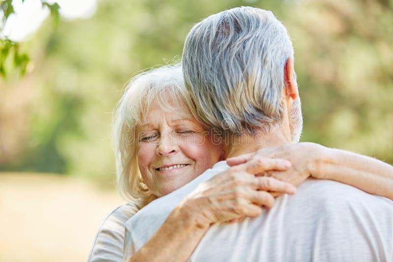 Gammal kvinna som kramar en gamal man royaltyfri foto