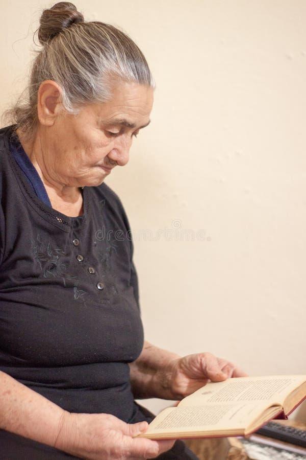 Gammal kvinna som läser en bok fotografering för bildbyråer