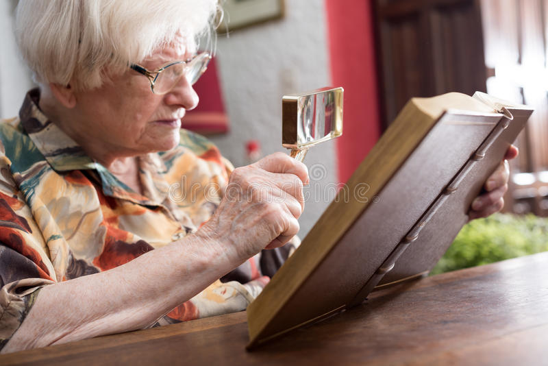 Gammal kvinna som läser en bok royaltyfria bilder