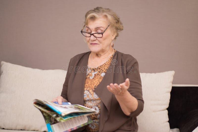 Gammal kvinna som läser en tidskrift arkivbild