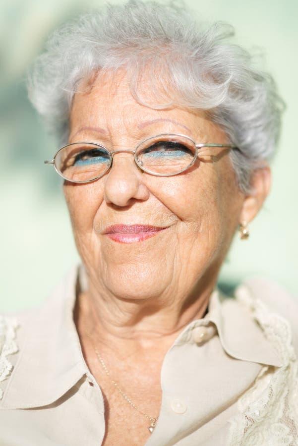 Gammal kvinna som ler och ser kameran arkivbilder