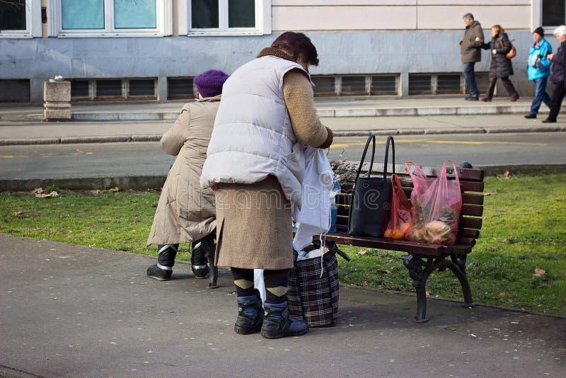 Gammal kvinna som packar henne påsar på bänken i parkera royaltyfri fotografi