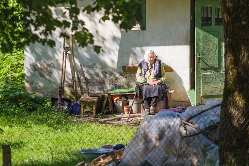 Gammal kvinna som placerar på trädgården stads- sikt för stad arkivfoton