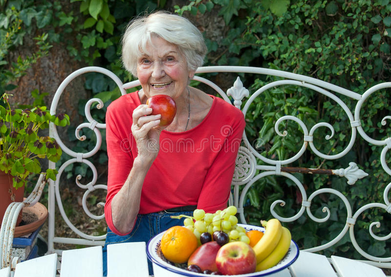 Gammal kvinna som rymmer en Apple på den trädgårds- tabellen arkivfoto