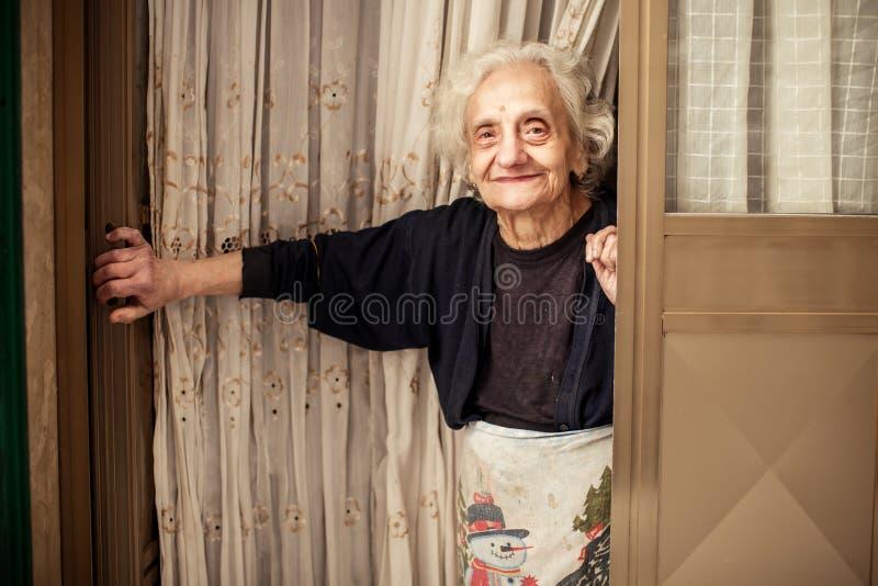 Gammal kvinna som ser ut ur dörren arkivfoton
