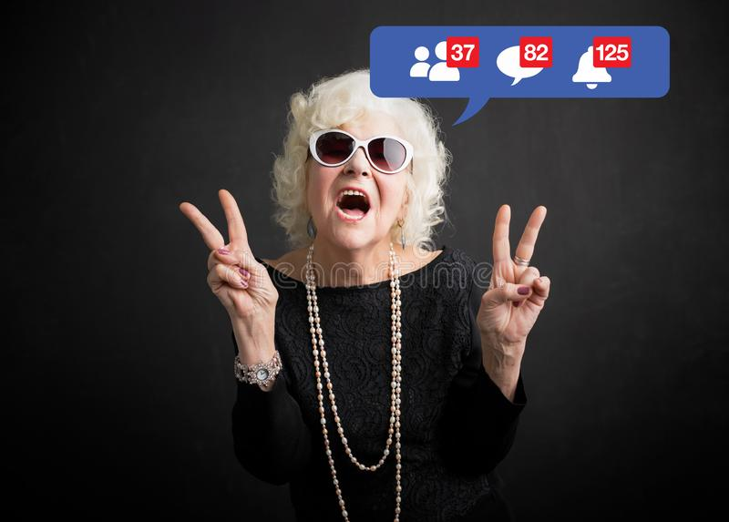 Gammal kvinna som vaggar och är fortfarande aktiv på socialt massmedia fotografering för bildbyråer