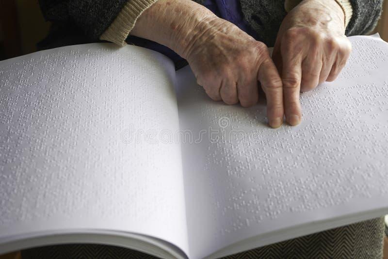 Gammal kvinnas händer som läser en bok med blindskriftspråk royaltyfria foton