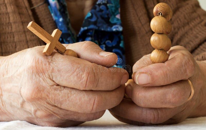 Gammal kvinnas händer som rymmer radbandet royaltyfria bilder