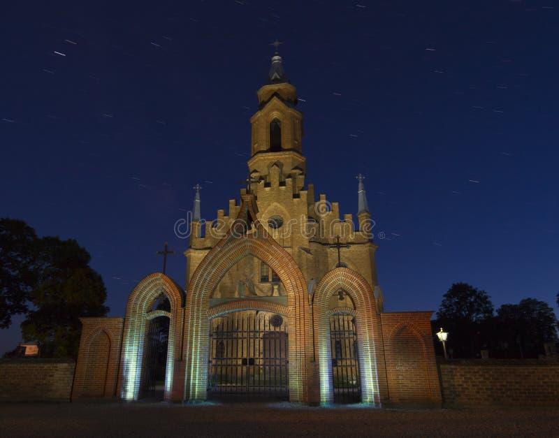 Gammal kyrka i den gotiska stilen på natten, Litauen royaltyfria foton