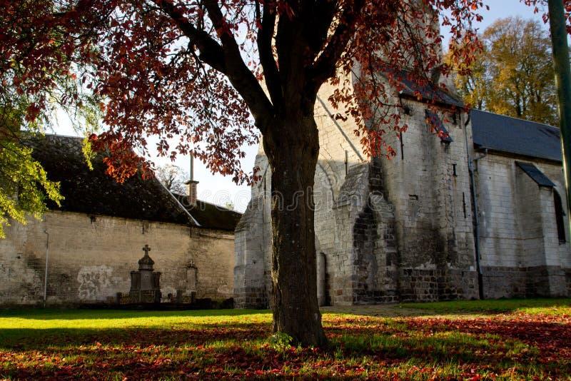 Gammal kyrka i en liten by i nord av Frankrike under höstsäsong royaltyfri fotografi