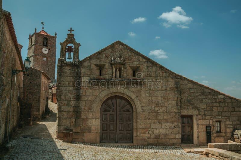 Gammal kyrka med stenväggen och kyrktorn i Monsanto arkivbilder